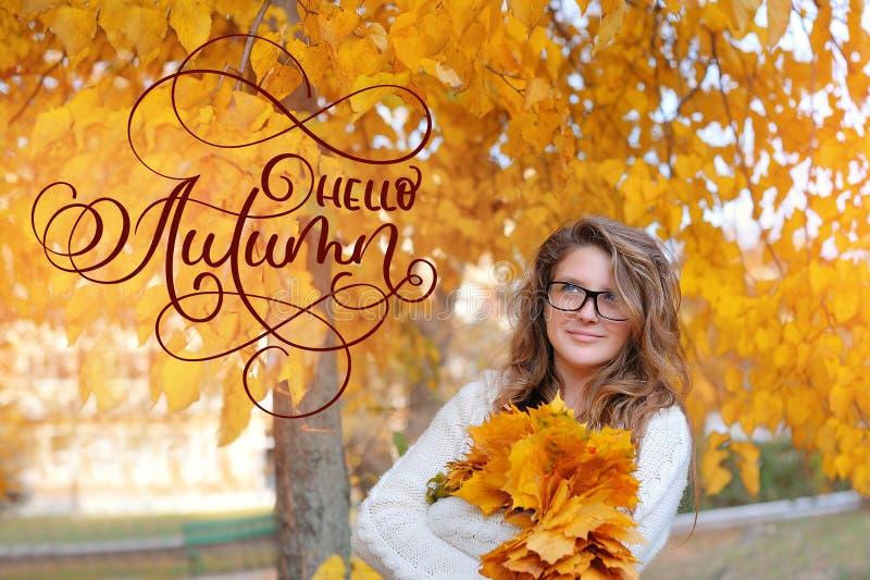 你好秋天书法字法文本 美丽的女孩在秋天视觉的玻璃在黄色地方教育局 图库摄影