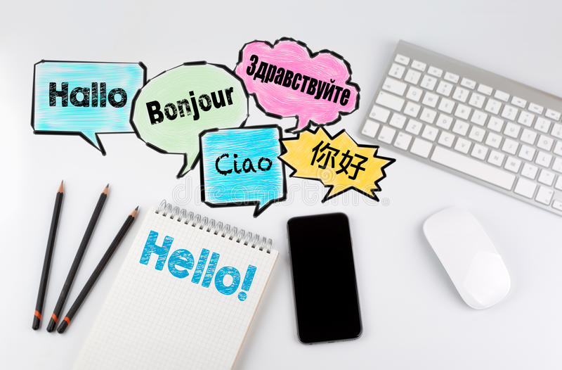 你好词云彩用世界的不同的语言,背景概念 与计算机、智能手机和笔记本的办公桌桌 免版税图库摄影