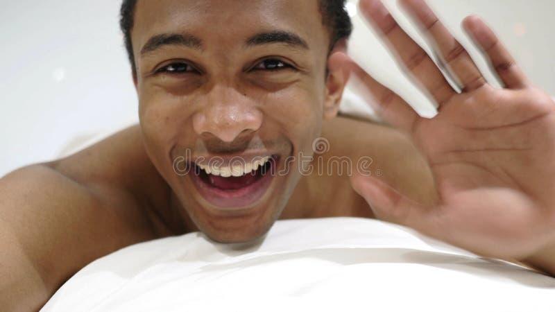你好,欢迎愉快的非洲人在床挥动的手上 免版税库存照片