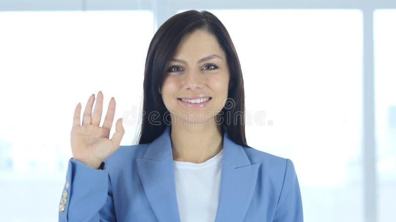 你好,正面年轻女实业家挥动的手 库存图片