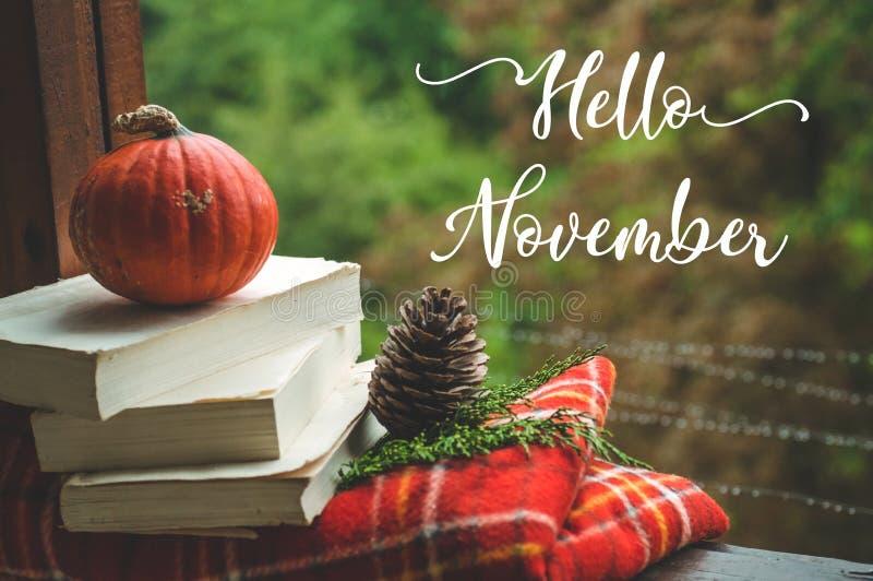 你好11月 舒适秋天静物画:托起并且打开了在葡萄酒窗台的书与红色毯子,南瓜,蜡烛 秋天 雨 库存图片