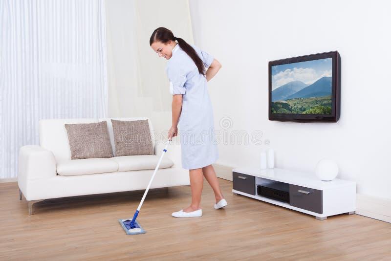 佣人与拖把的清洁地板 免版税库存图片