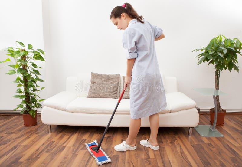 年轻佣人清洁地板 库存图片