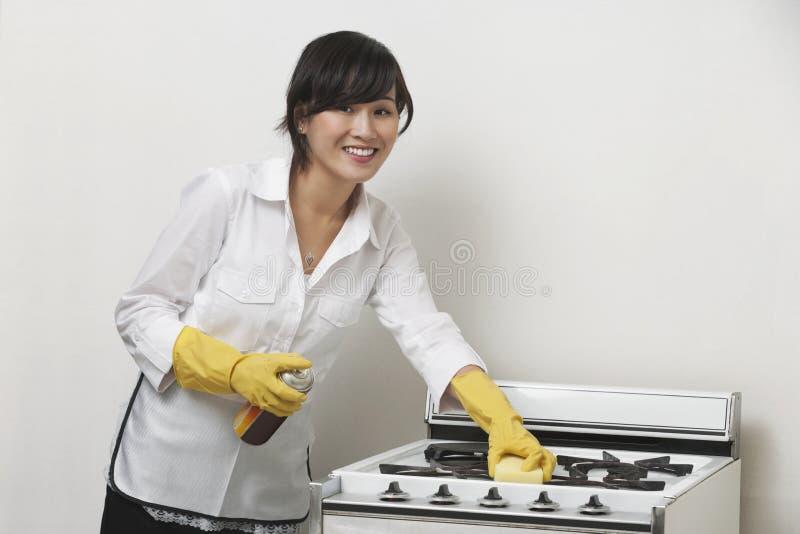 年轻佣人清洁火炉画象反对灰色背景的 库存图片