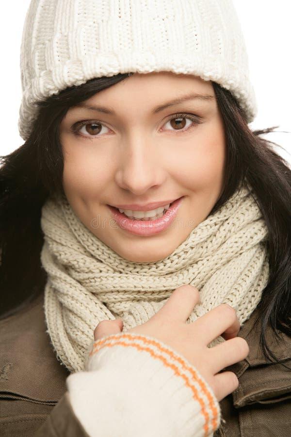 佩带一个冬天的微笑的美丽的友好的年轻深色的妇女 免版税库存照片