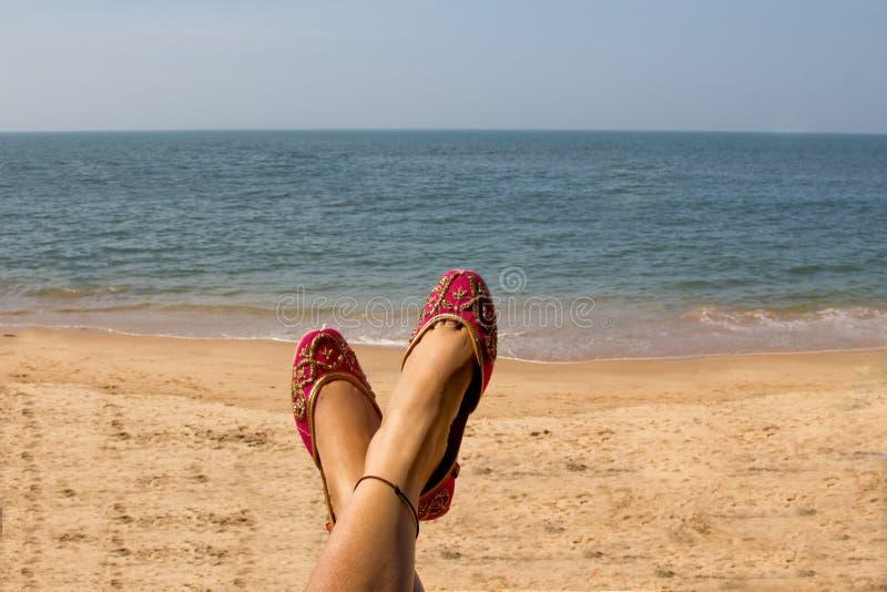 佩带一个对桃红色传统印地安妇女` s的夫人穿上鞋子jutis在Anjuna海滩在果阿,印度 免版税库存图片