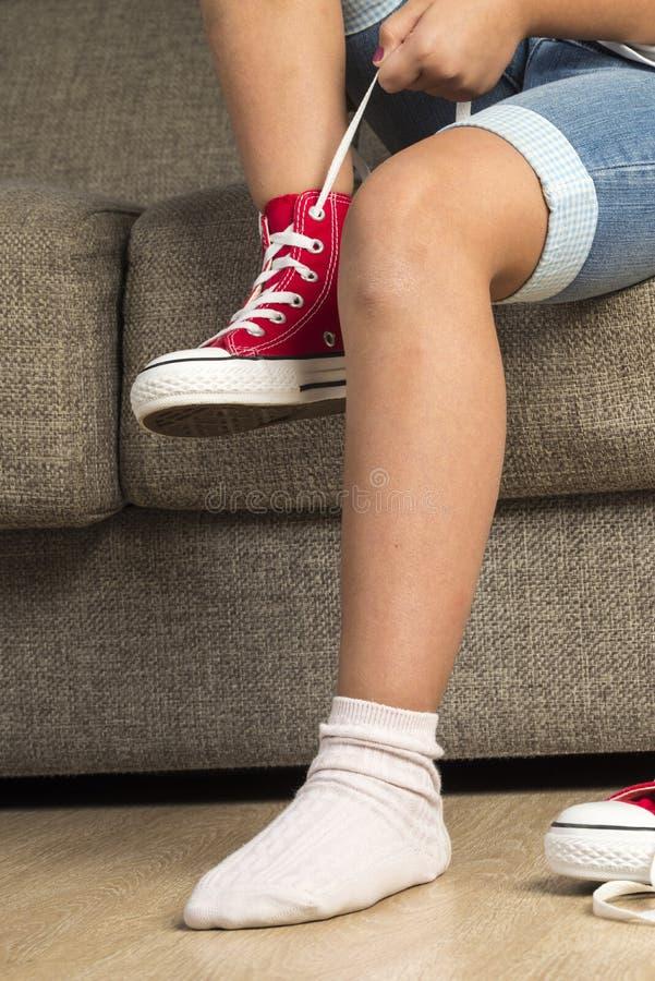佩带一个对红色运动鞋的女孩 库存图片