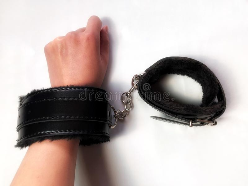 佩带一个对黑毛茸的皮革性玩具手铐的妇女手 免版税库存照片