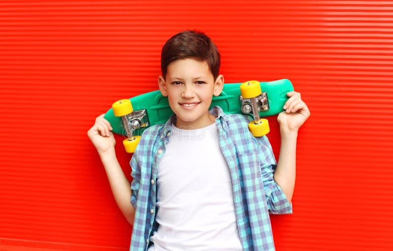 佩带一个方格的shirtwith滑板的画象愉快的微笑的少年男孩在城市 库存图片