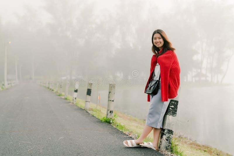 佩带一个红色毛线衣身分的亚裔少年微笑在沿水库的路在早晨薄雾和早晨阳光 免版税库存图片