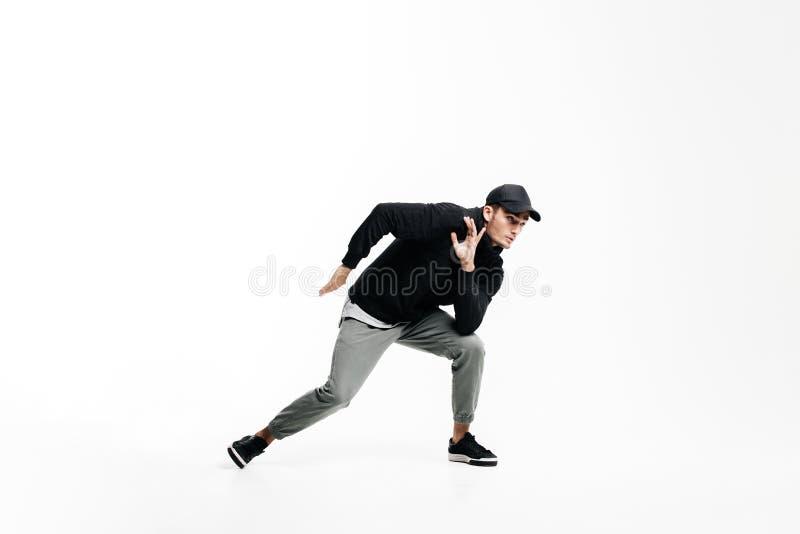 佩带一个黑运动衫、灰色裤子和盖帽跳舞街道舞蹈在白色背景的英俊的年轻人 免版税库存图片
