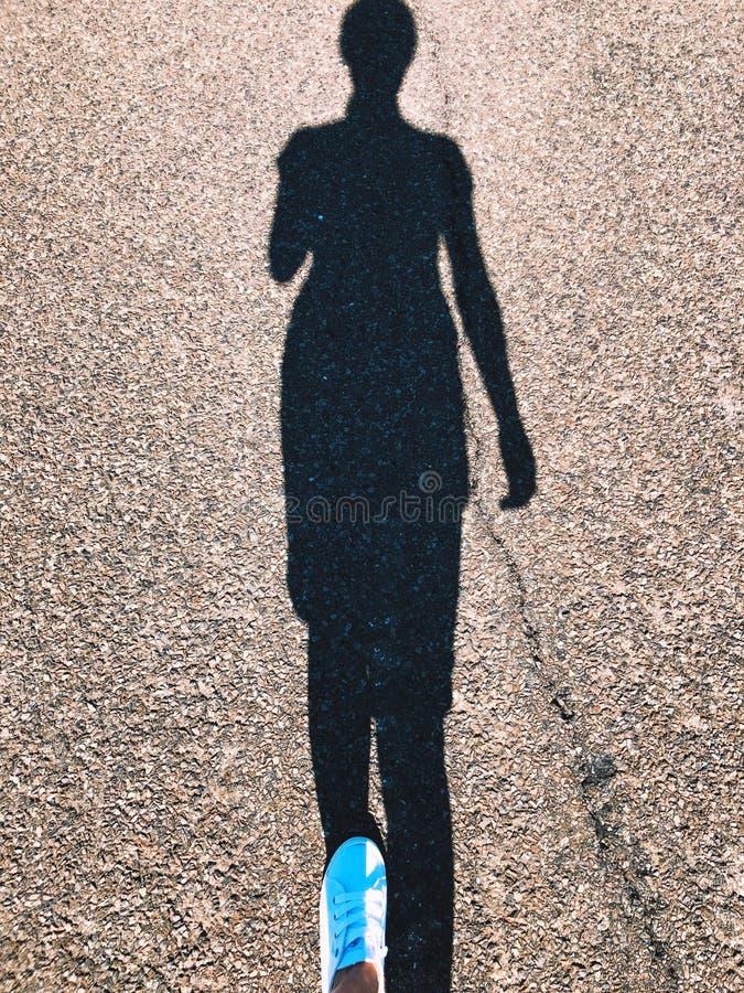 佩带一双白色运动鞋的妇女走在有阴影的路在地面上 免版税库存照片