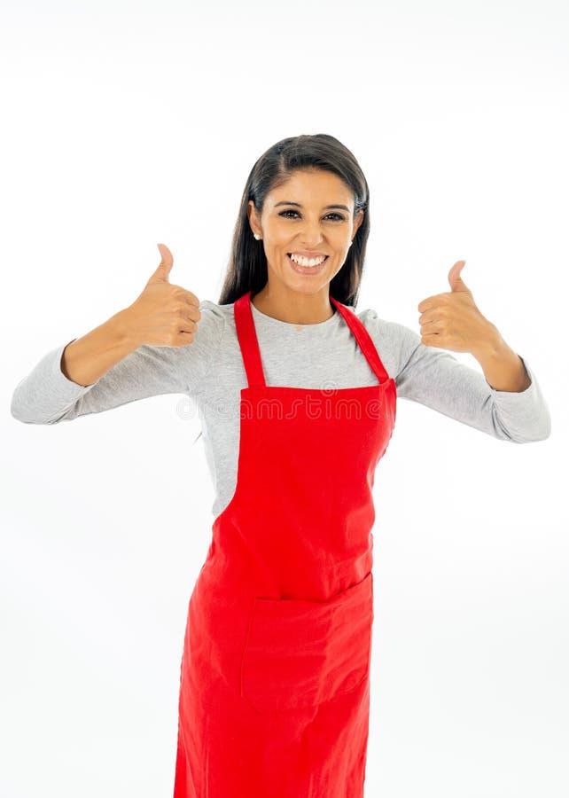 佩带一条红色围裙的一名愉快的骄傲的美丽的拉丁妇女的画象学会烹调做在烹饪课的赞许姿态 图库摄影