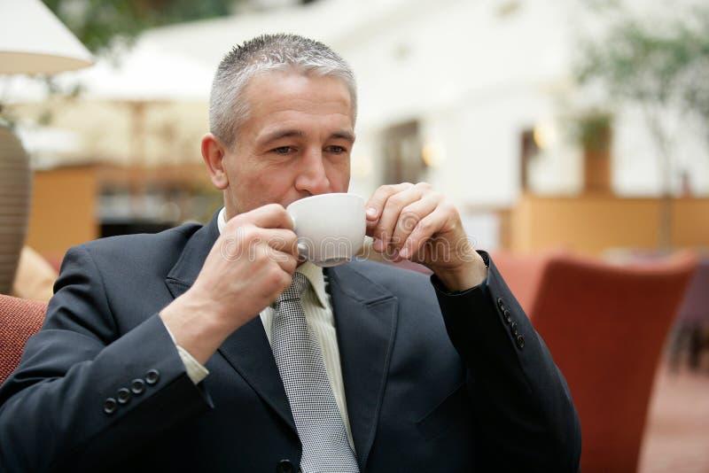 佩带一杯衣服饮用的咖啡的英俊的资深商人 库存照片