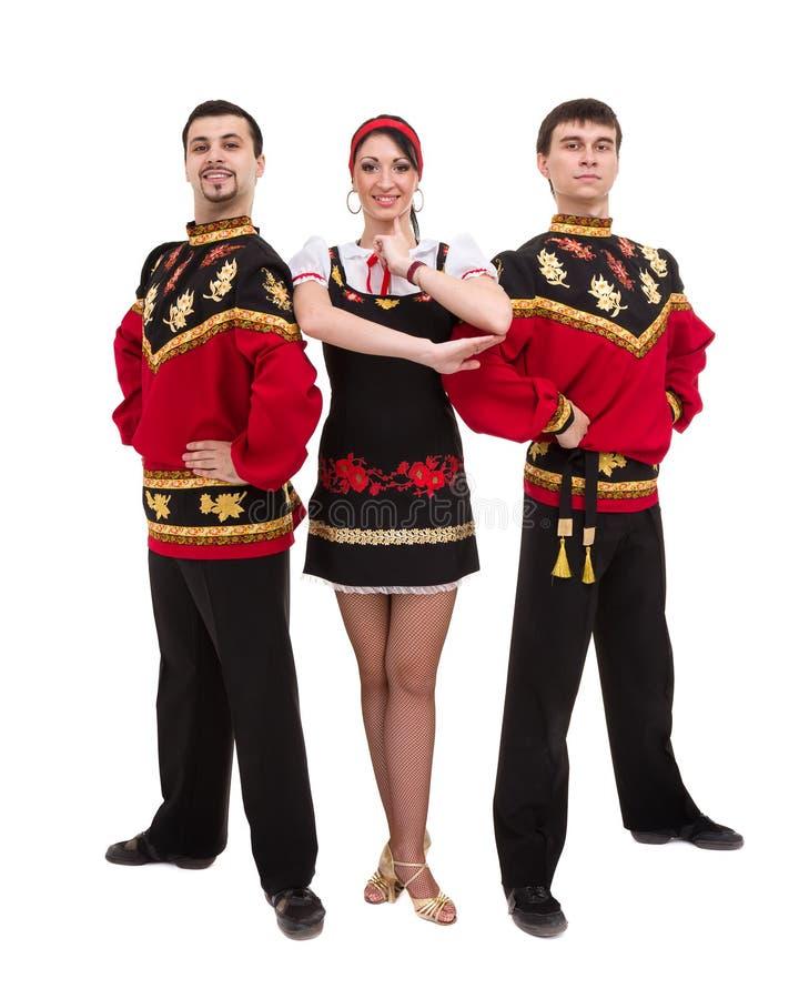 佩带一民间俄国服装摆在的两个男人和一名妇女 免版税库存照片