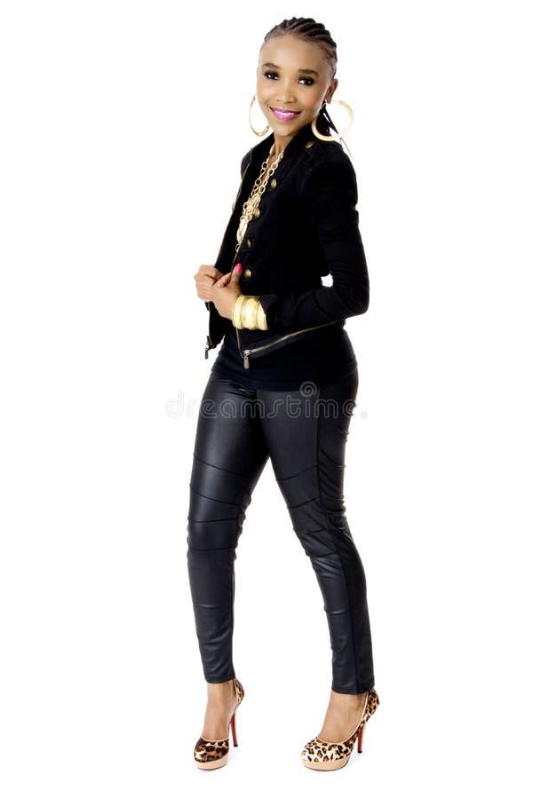 佩带一片黑夹克金黄首饰和桃红色嘴唇的年轻美丽的非洲妇女 免版税库存图片