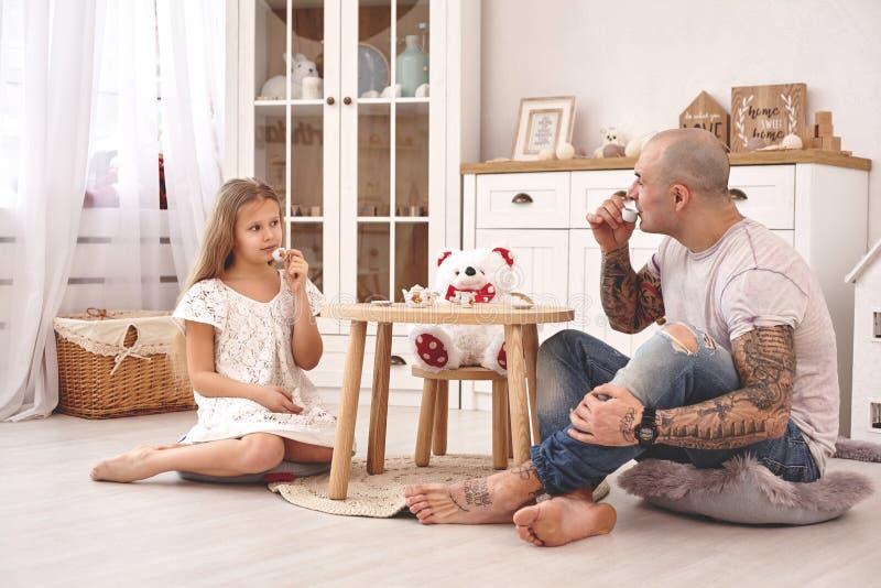 佩带一白色礼服whith的可爱的女儿她爱恋的父亲 他们喝从玩具盘的茶在一个现代孩子 库存图片