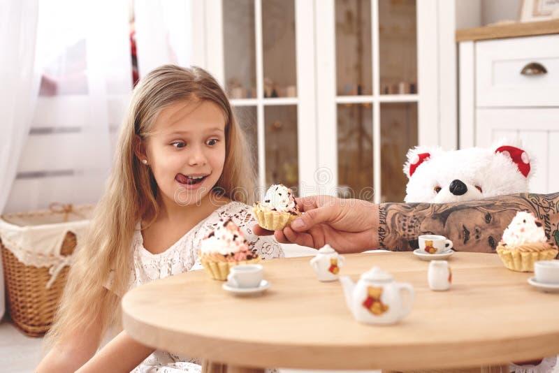 佩带一白色礼服whith的可爱的女儿她爱恋的父亲 他们喝从玩具盘的茶在一个现代孩子 库存照片