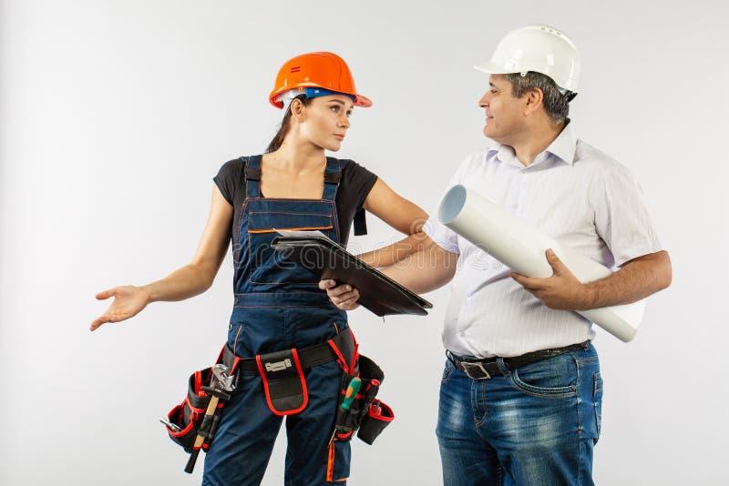 佩带一顶安全帽或盔甲和工友建造者妇女回顾的图纸的一个建筑师人 库存照片