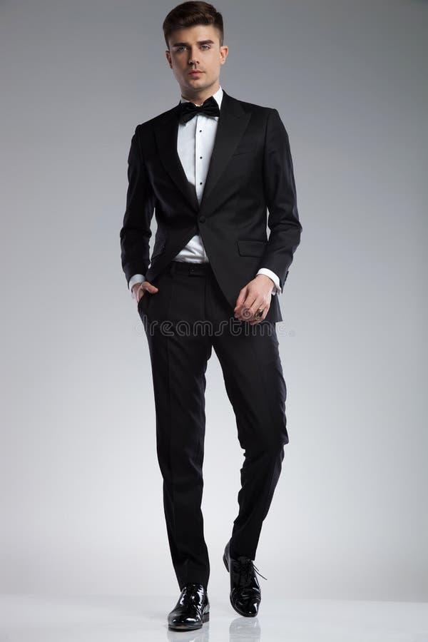 佩带一黑无尾礼服走的轻松的时髦的人 库存图片