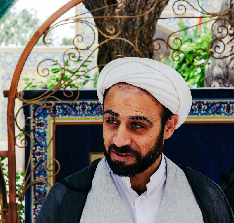 佩带一keffiyeh的年轻伊朗毛拉的画象在Jame清真寺庭院里  免版税库存照片