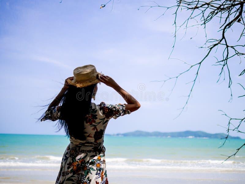 佩带与帽子的亚裔妇女漂泊礼服样式站立在看对白色海滩和波浪的海岸与蓝天 库存图片