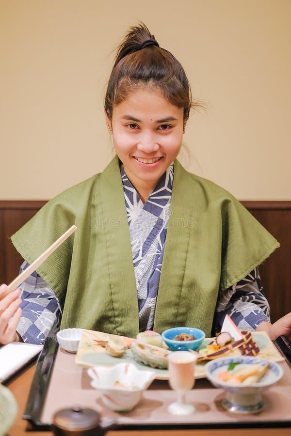 佩带与日本餐具和开胃菜的年轻亚裔妇女Yukata在传统ryokan手段的木桌上在 图库摄影