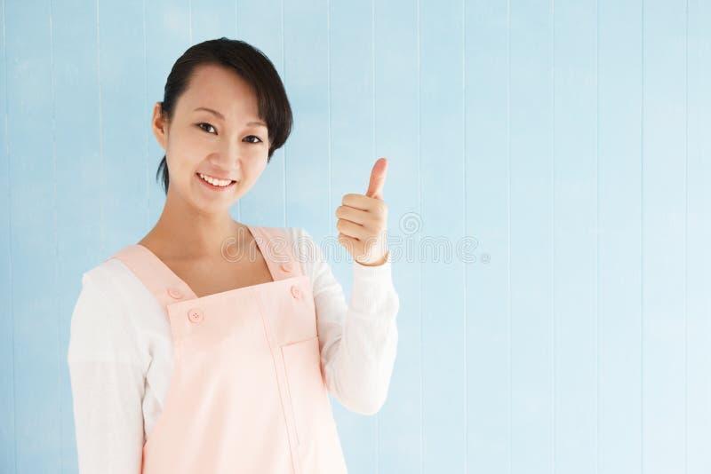 佩带与赞许的亚裔妇女一条围裙 免版税库存图片