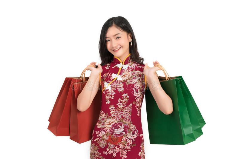 佩带中国礼服举行购物带来cheongsam,qipao微笑的亚裔妇女在春节 免版税库存图片