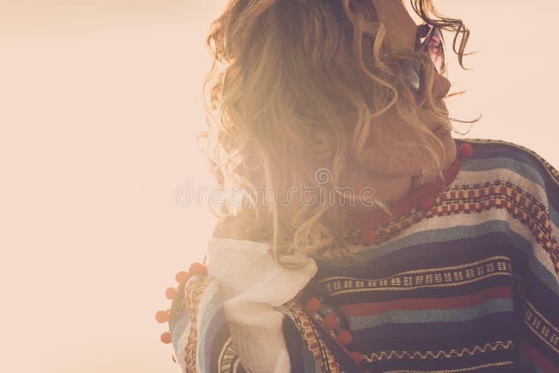 佩带为美丽的式样中年好妇女的嬉皮的墨西哥样式雨披室外与风在天空中和unglasses在a期间 免版税库存照片