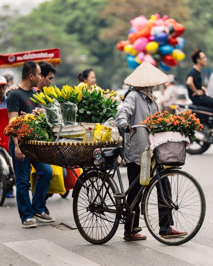 佩带亚洲圆锥形帽子出售的越南妇女在她的自行车开花在河内,越南街道  库存图片
