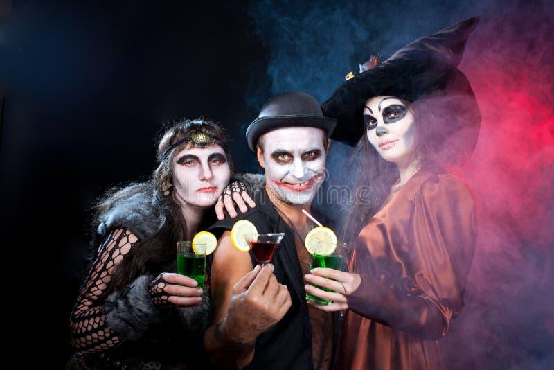 佩带作为吸血鬼和巫婆的男人和妇女。万圣夜 免版税库存照片