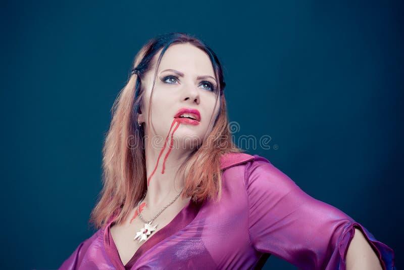 佩带作为吸血鬼的妇女为万圣夜 库存照片