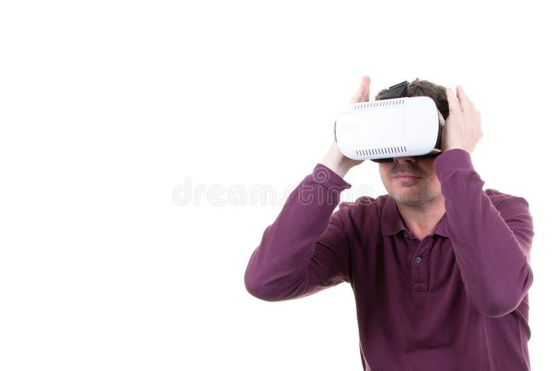 佩带使用虚拟现实VR玻璃在白色背景的盔甲耳机的人 智能手机使用与虚拟现实风镜 免版税库存照片