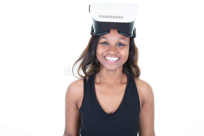 佩带使用虚拟现实VR玻璃在白色背景的盔甲耳机的微笑年轻女人 库存图片