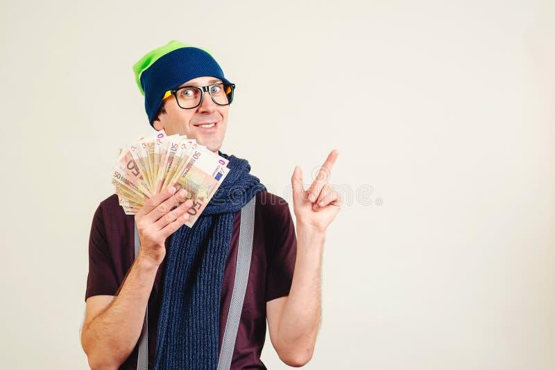 佩带倒栽跳水的玻璃的滑稽的人拿着金钱和指向在空的拷贝空间 有钞票的男性书呆子在白色 人礼物 免版税库存照片