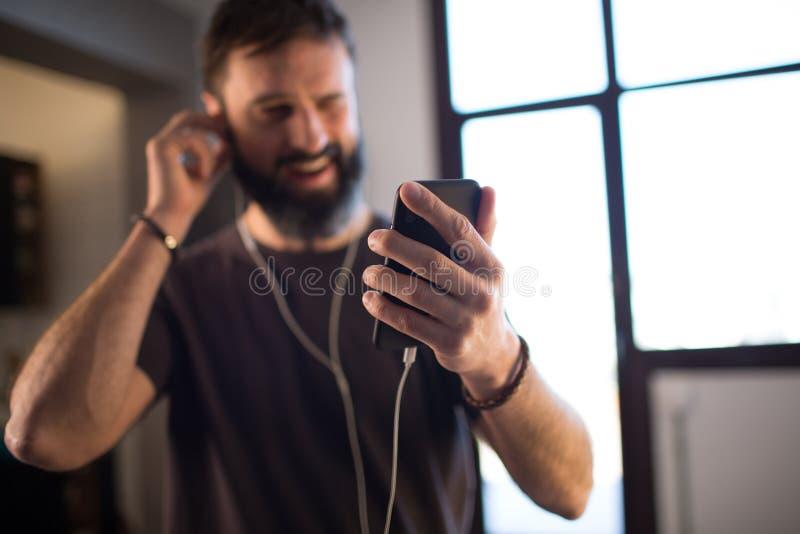 佩带偶然灰色在耳机的年轻有胡子的人T恤杉听的音乐,检查在智能手机的人脉 免版税库存图片