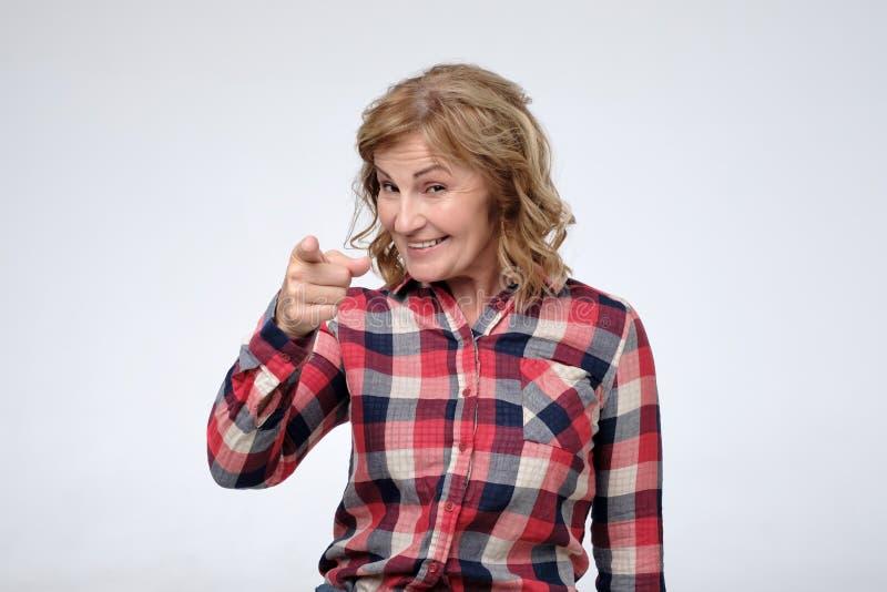佩带偶然衬衣微笑的指向与食指的照相机的成熟白种人妇女 库存图片