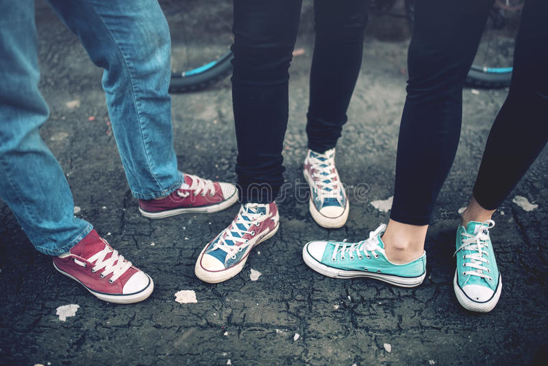 佩带偶然运动鞋的年轻人反叛少年,走在肮脏的混凝土 帆布鞋和运动鞋在女性成人 库存照片