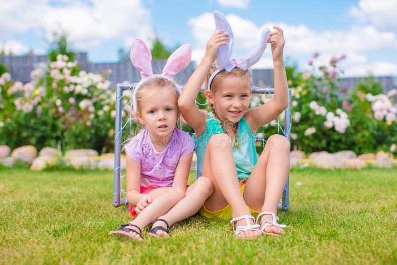 佩带兔宝宝耳朵的两个可爱的妹在复活节天户外 库存照片
