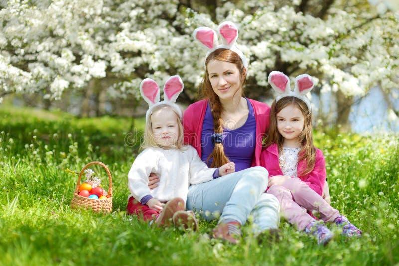 年轻佩带兔宝宝耳朵的母亲和她的女儿在复活节天 图库摄影