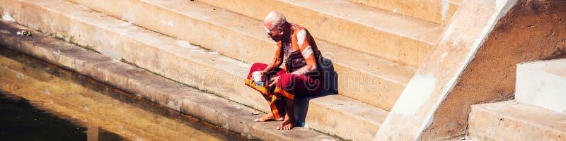 佩带典型的长袍选址的老人在Sree Padmanabhaswamy寺庙水池在晴天期间在特里凡德琅,印度 免版税库存照片