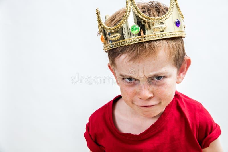 佩带冠的一个小男孩的生气的滑稽的面孔 免版税库存图片