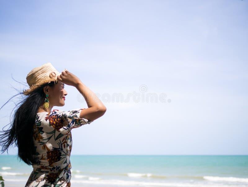 佩带减速火箭的衣物样式的美丽的亚裔妇女恭敬地举行和站立在看对白色海滩和波浪的海边 免版税图库摄影