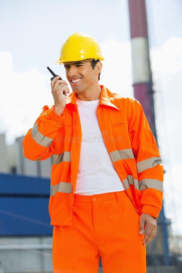 佩带反射性工作服的愉快的建筑师沟通在携带无线电话在站点 库存照片