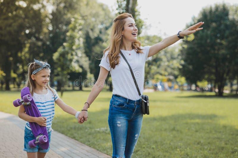 佩带发怒书包的时髦的母亲有与女儿的步行 图库摄影