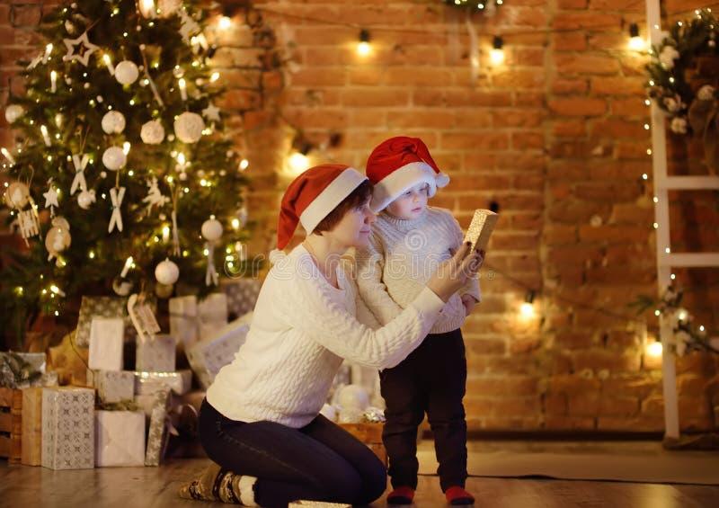 佩带圣诞老人帽子和他的母亲或祖母尊敬的逗人喜爱的小男孩圣诞节礼物 愉快的家庭画象在圣诞前夕的 免版税库存照片