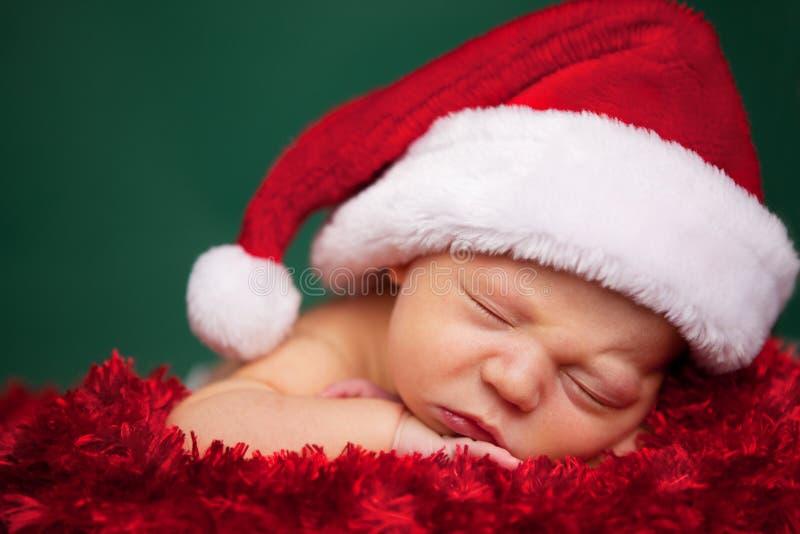 佩带圣诞老人帽子和睡觉的圣诞节新生儿 库存图片