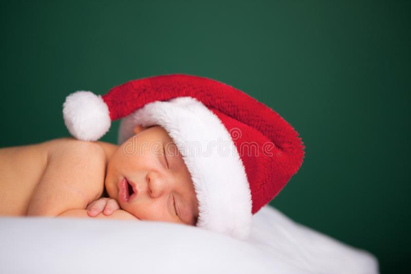 佩带圣诞老人帽子和睡觉的圣诞节新生儿 免版税库存照片