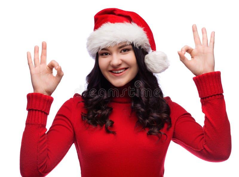 佩带圣诞老人帽子和确信的做的好姿态的快乐的妇女画象,被隔绝 免版税库存图片